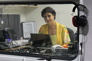 A woman sits in a sealed off booth looking at a computer. On this side of the window hangs a pair of earphones