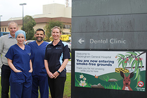 Two male and two female RkPG staff members stand beside a sign reading 'Welcome to Rockingham General Hospital. You are now entering smoke free grounds'.